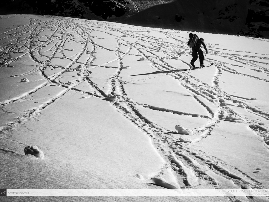Brian Fletcher climbing through snow textured by warm rolling snowballs en route to Cache Col and Spider Mountain.