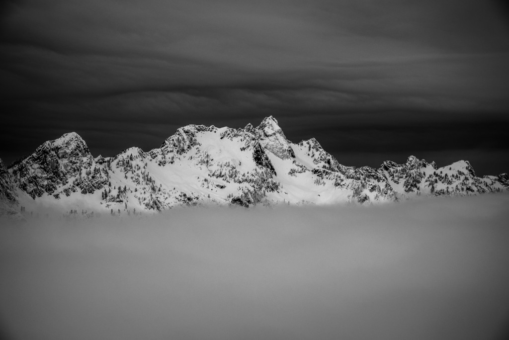 Fog at pass level and dark clouds above, but perfect visibility in the alpine terrain around Chair Peak as seen from Guye Peak.