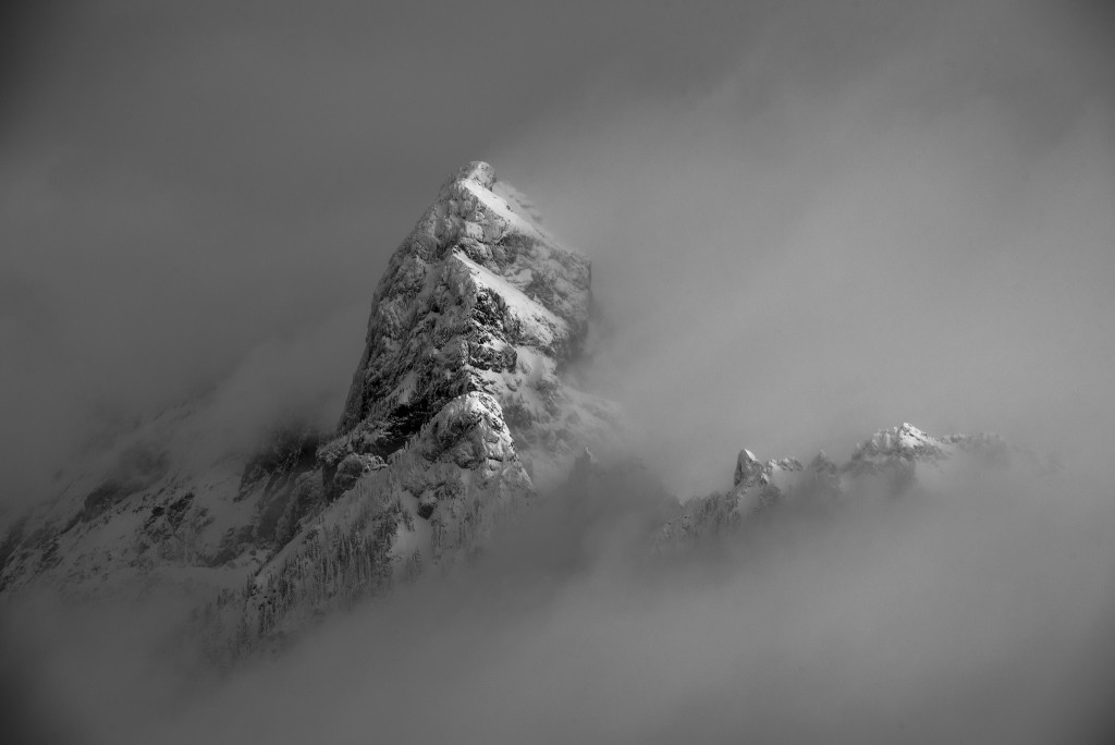 The spectacular summit of Mt. Thompson makes a dramatic appearance through swirling clouds.